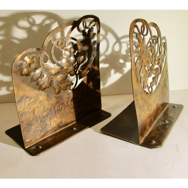 """Pierced copper arts and craft pair of bookends in motif of grape leaves and fruit with scrolling vines. Size 7.5""""tall,..."""
