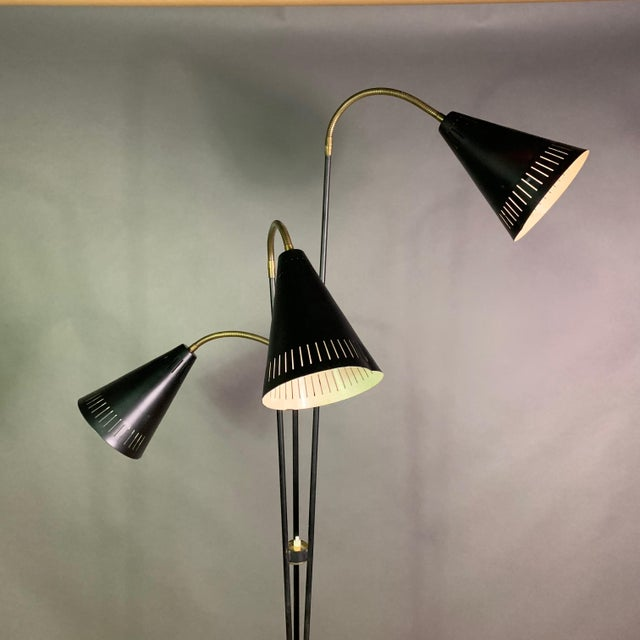 Classic Scandinavian mid-century floor lamp with three black-lacquered and perforated metal cones on brass articulating...