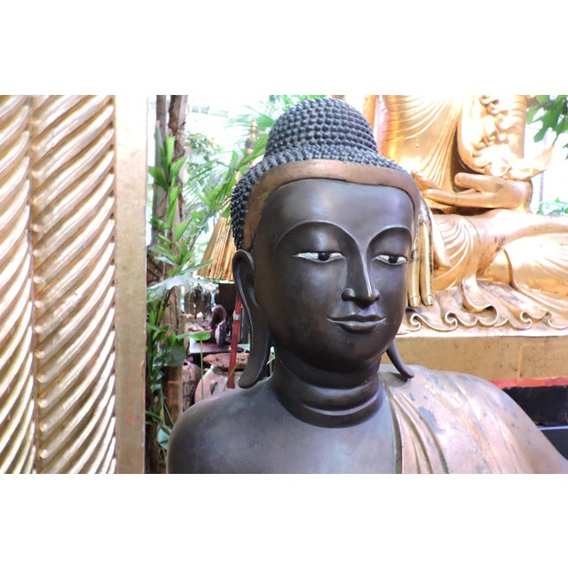 Smooth skinned dark gray-charcoal 19th Century Buddha with gold robe and white fingernails. An amazing presence seeming to...