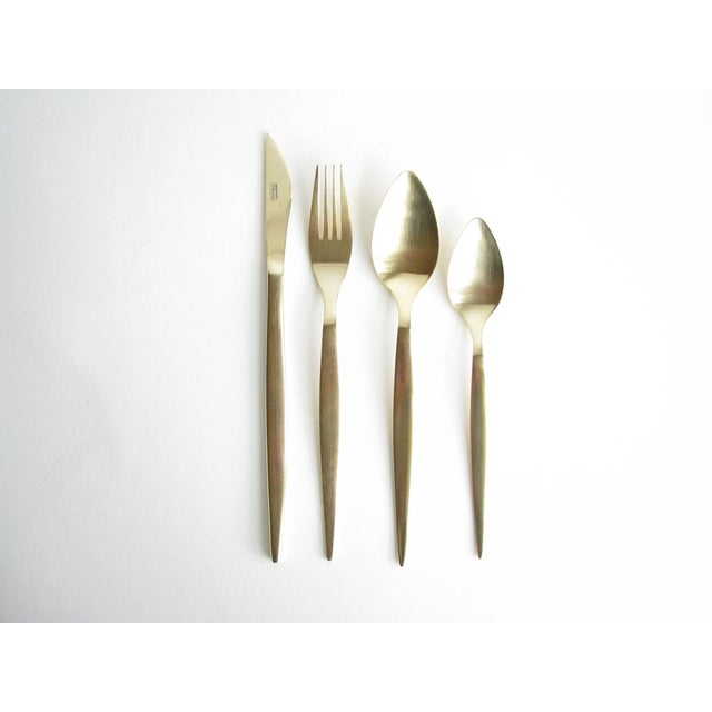 Stunning modern Guttlem Germany gold brushed stainless steel flatware set. There are 24 pieces: 6 knives, 6 forks, 6...