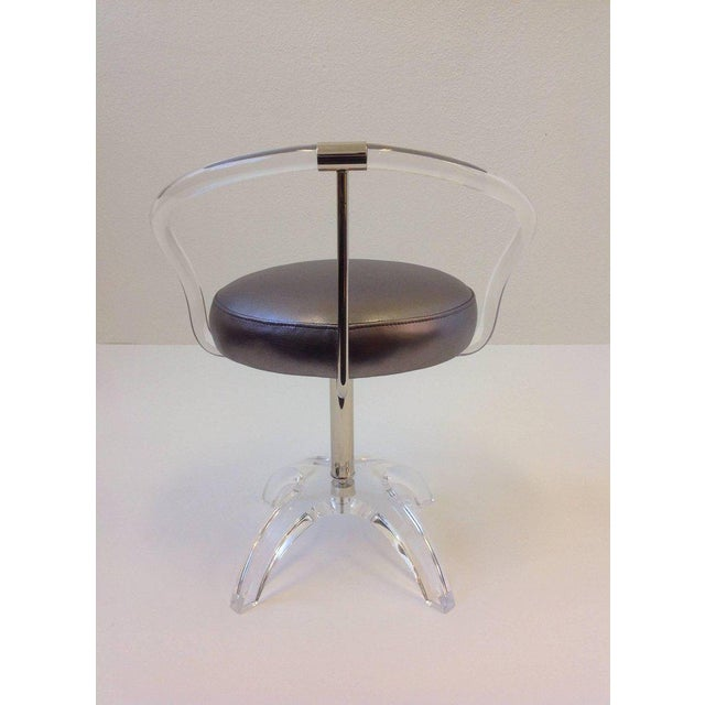 A glamorous clear acrylic and polished nickel with a metallic silver leather seat vanity stool. The stool Swivels 360...