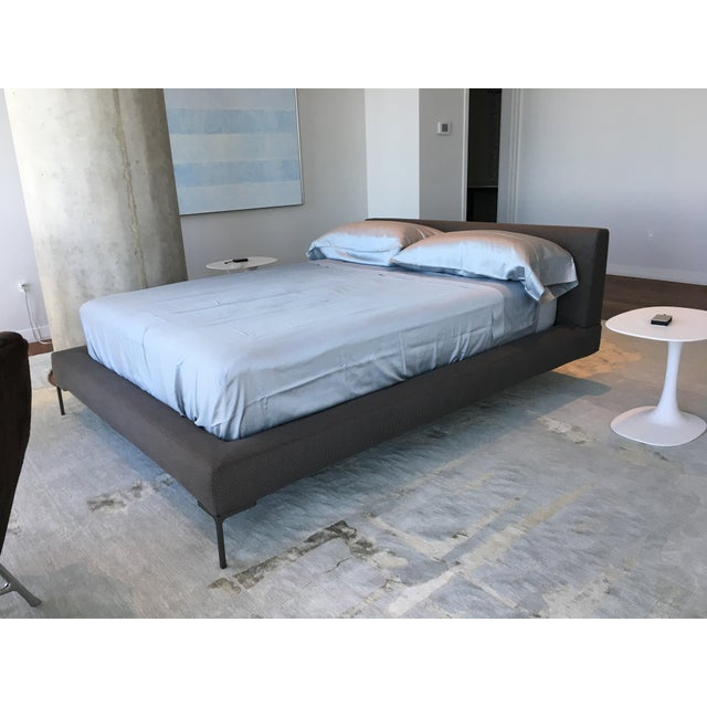 This is a B & B Italia bed from the Charles collection designed by Antonio Citterio. It has a cushioned headboard, and...