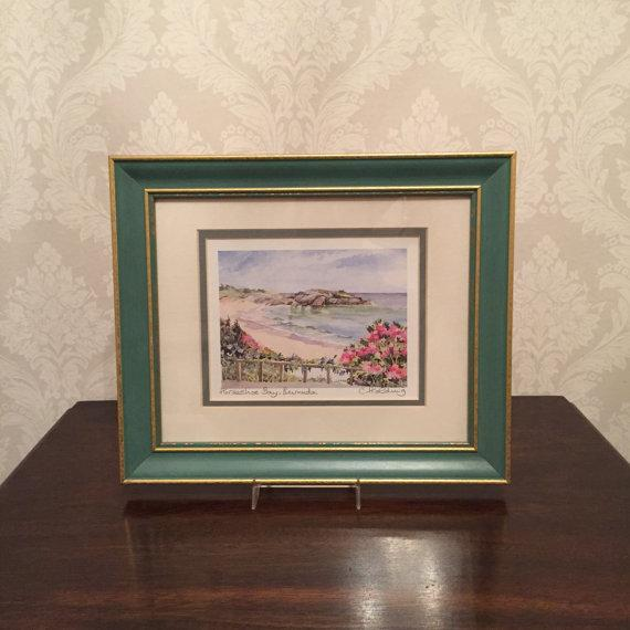 This is a beautiful framed print of a watercolor of Horseshoe Bay Beach in Bermuda by Carole Holding. The piece is in...