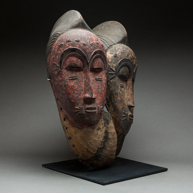 This serene bicephalous mask was made by the baule of the ivory coast area. It is in the semi helmet-mask format, with a...