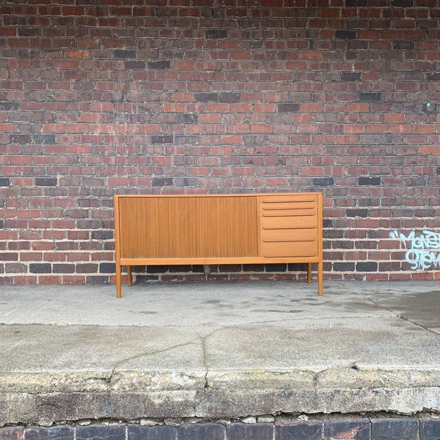 This beautiful light teak danish credenza is in great vintage condition. It has a large tambour door, rounded edges and is...
