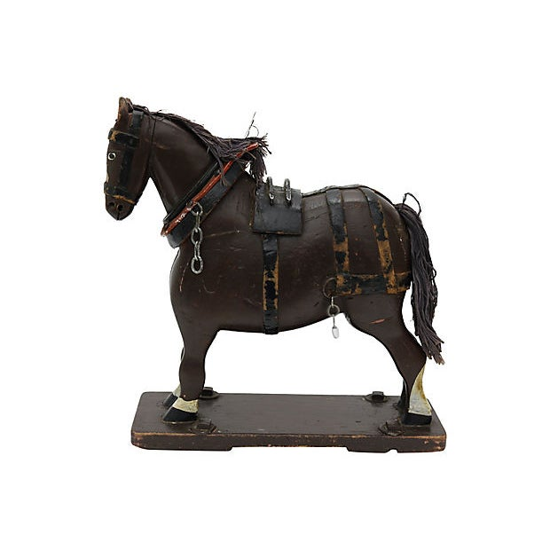 Antique French Folk Art wood horse. He sits upon a wood platform with brass wheels. No maker's mark. Wear to leather,...