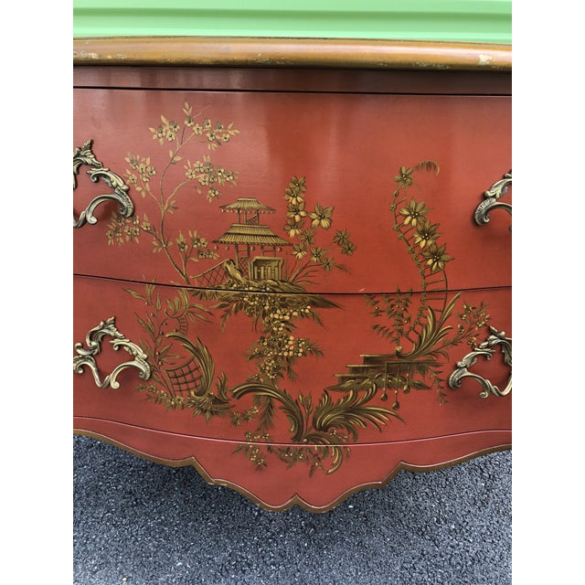 Solid wood chest of drawers in a rich reddish orange color with hand painted chinoiserie design. All original.