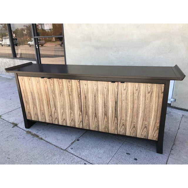 This sideboard is made of ebonized walnut for the body and bleached rosewood for the four doors which open on a shelf on...