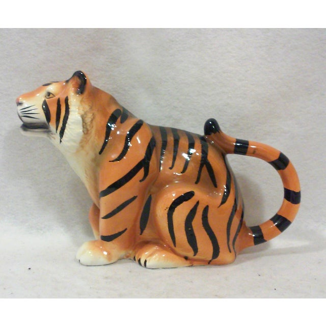 Ceramic tiger pitcher or creamer hand painted with black tiger stripes against an orange background with intricate...