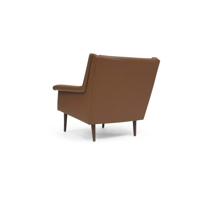 Lounge chair designed by Milo Baughman for Thayer Coggin upholstered in brown leather raised on solid walnut legs.