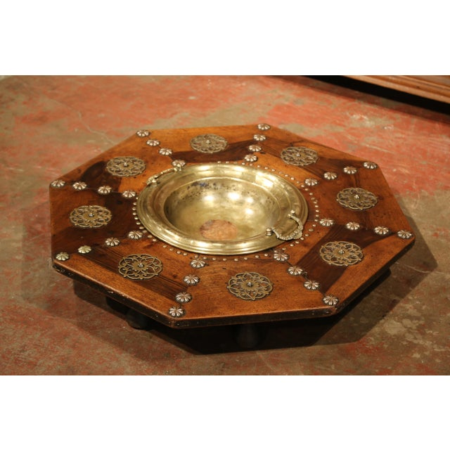 This elegant and unusual fruitwood table with a decorative brass bowl was created in Spain, circa 1800. The ornate,...