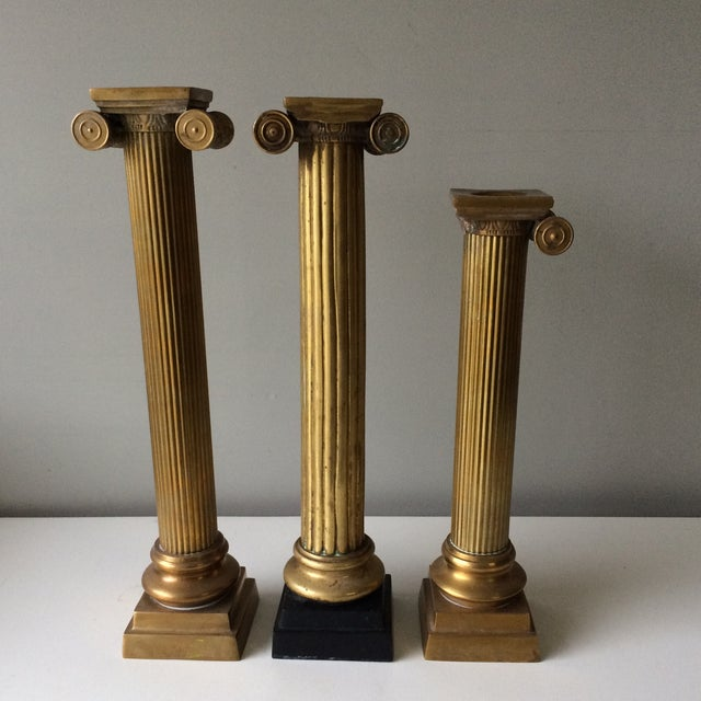 Set of three brass column pillar candleholders. One is missing a scroll, which does not take away from the integrity of...