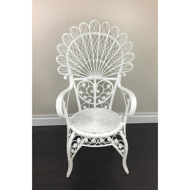 Ornate antique white wicker chair would make a great accent piece. Bent wicker scroll work and fan-like back.