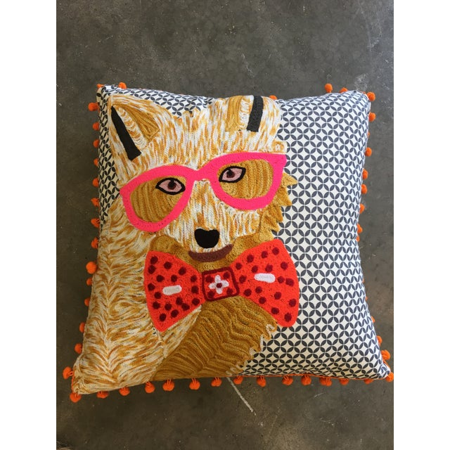 This is a pillow by Karma Living featuring a fox with glasses and pom-pom trim