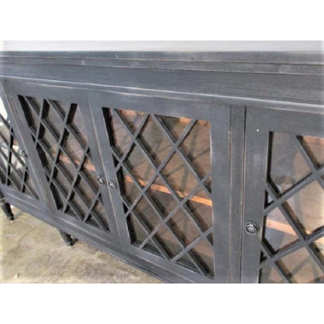 This is a charcoal black colored sideboard with glass doors with a chriss cross pattern. It is made of mahogany. The...