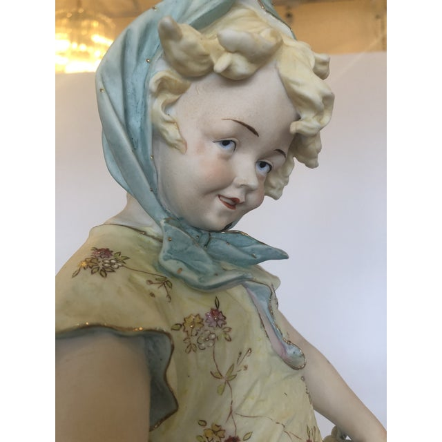 A tall meticulously detailed and hand painted parian porcelain figure of a country girl having blue bonnet and holding...