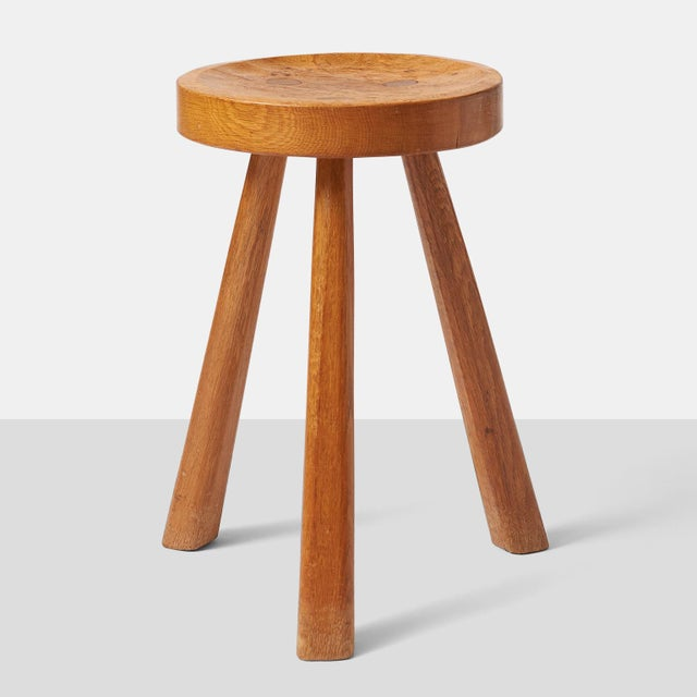 A rare oak stool on three square legs and a beautifully carved seat, by Jean Touret for Atelier Marolles. The stool is...