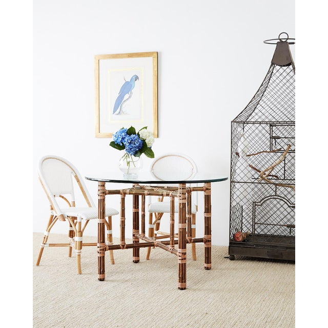 """Pair of white French bistro or cafe style """"Riviera"""" chairs featuring bamboo rattan frames with hand-woven upholstery...."""