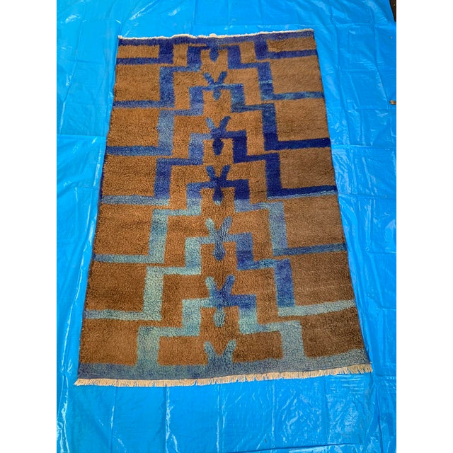 Soft and sumptuous medium shag wool rug in brown and blue hues.