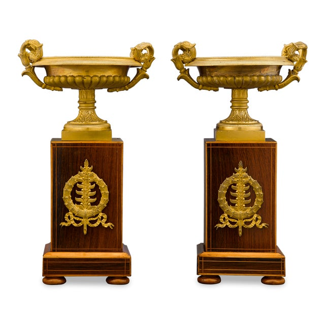 A gracious pair of bronze ormolu, Greco-Roman inspired urns, set upon Charles X-style stands of inlaid wood. Bronze ormolu...