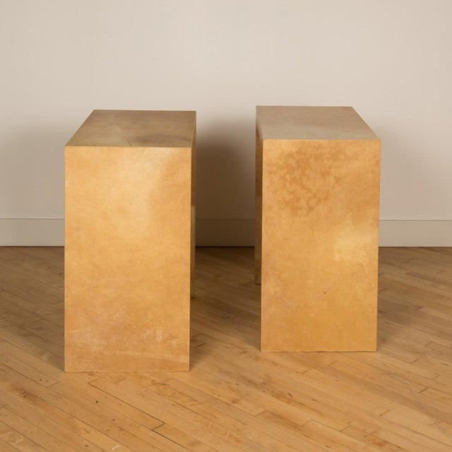A pair of tall small parchment consoles, in the manner of Jean-Michel Frank.