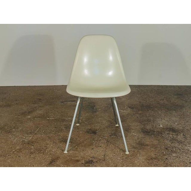 White Eames fiberglass shell chairs on original H bases. Narrow mount. Twelve available. All chairs are stamped. Other...