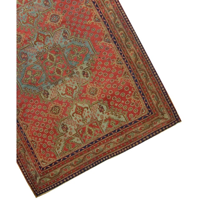 Three central medallions woven in blues reds and chocolate fill the resplendent red central field of this antique Oushak...