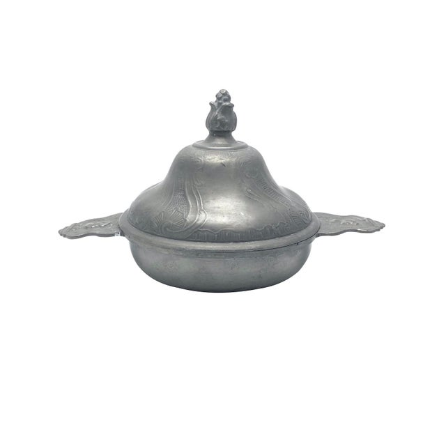 A Nineteenth Century Continental pewter porringer and cover. The cover is bell-shaped with a foliate finial. The porringer...