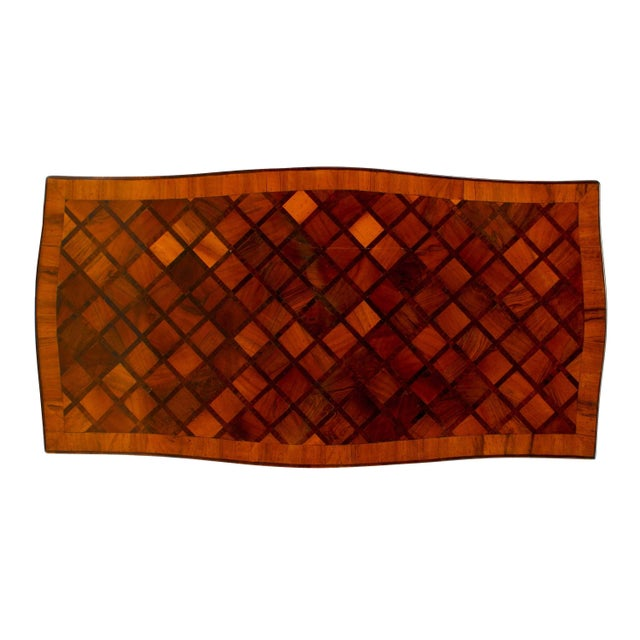 French Louis XV style 20th century walnut and fruitwood coffee table with a shaped top inlaid with parquetry design of...