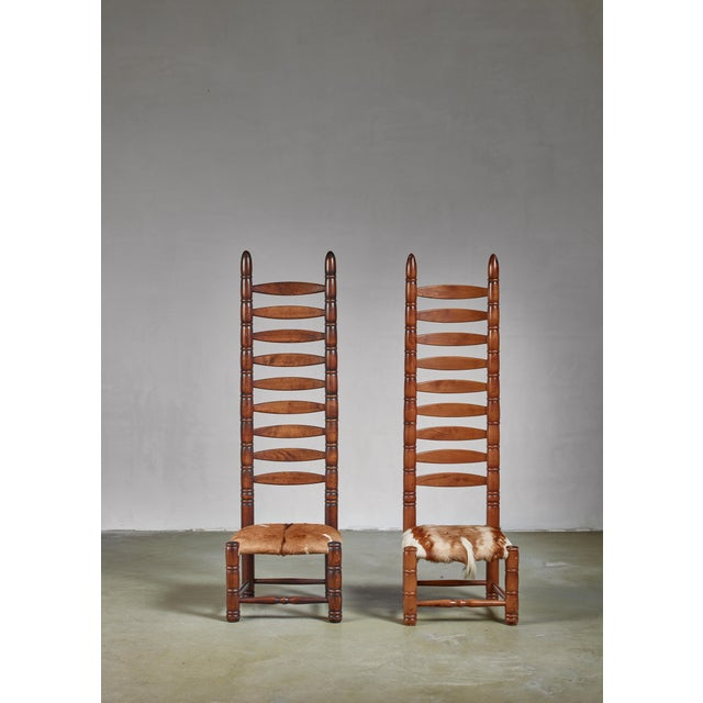 A pair of decorative bohemian object chairs from the 1960s. This matching pair of high back ladder chairs is upholstered...