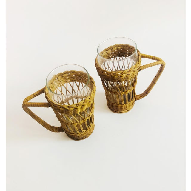 A set of 2 vintage boho glasses with wicker holders. Each holder has a lovely woven pattern and sturdy handle. Perfect for...