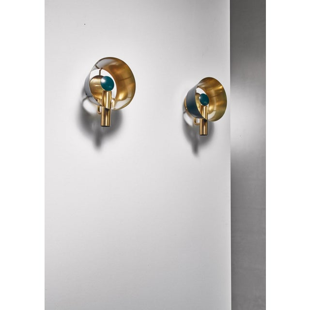 A pair of brass wall lamps, partly lacquered green, by Lyfa. The lamp has a adjustable deflector in front of the light...