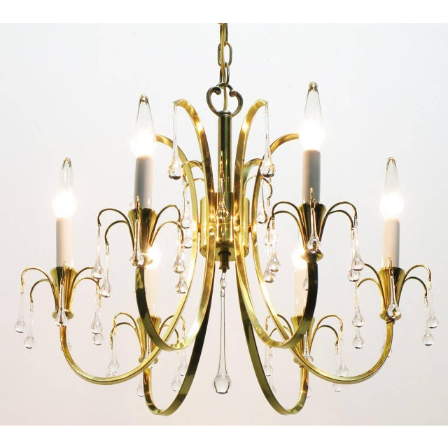 Modernist crystal chandelier with six C-curve arms and brass end cups. Raindrop crystals hang from every arm, with long...