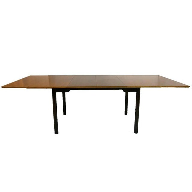 Sleek walnut extension dining table with deep mahogany base and legs. Each leg is wrapped with a stunning leather detail...