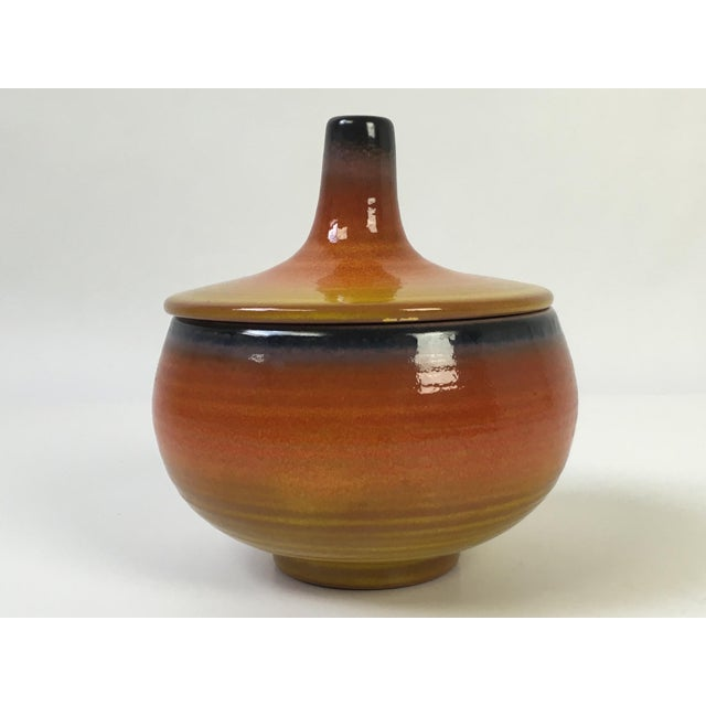 A vibrantly colored, early american Haeger ceramic covered pottery dish. Orange with hues of yellow and brown. Small chip...