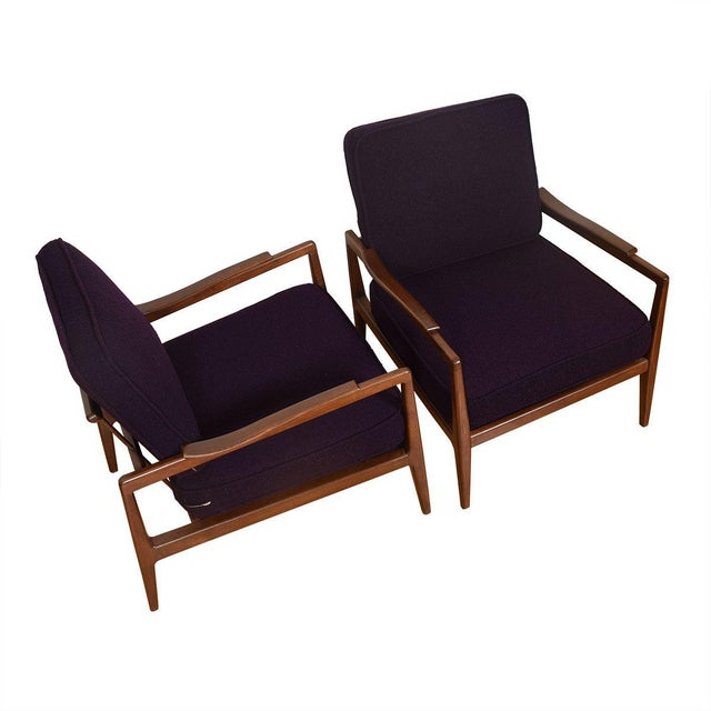 We are pleased to offer this pair of beautiful walnut club chairs attributed to Edmond Spence. The arms of the chair have...