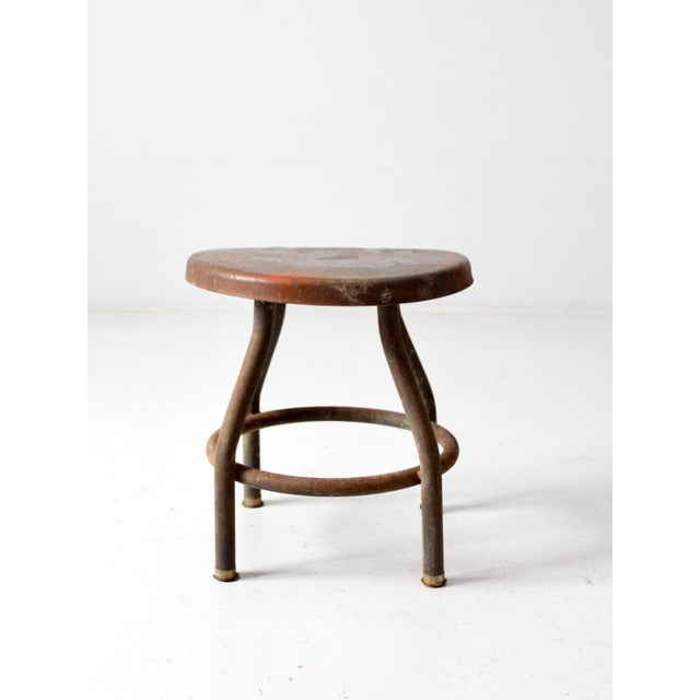 This is a vintage industrial stool. The short metal stool sloped seat with four legs and central stretcher.