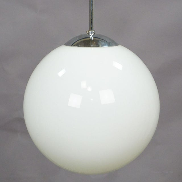 an antique bauhaus style pendant lamp with a large white opaline glass shade and cromium plated metal suspension. cabling...