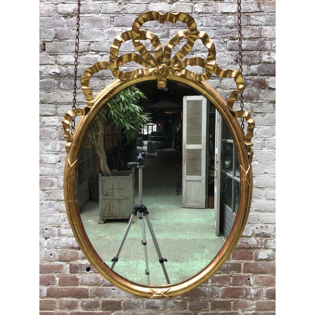 early 19th century mirror, in the style of Louis XVI, Provenance France Nice oval mirror with a elaborate ribbon on top....