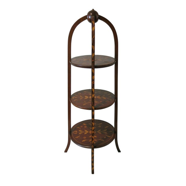 A late 19th Century mahogany three tiered muffineer stan. The stand with three arched legs decorated with floral marquetry...