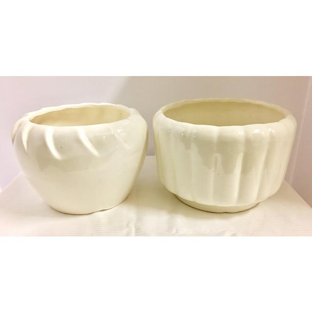 Vintage pair of polished white planters or vases. One has a pinched rim and the other is ribbed. The left one: Stamped...