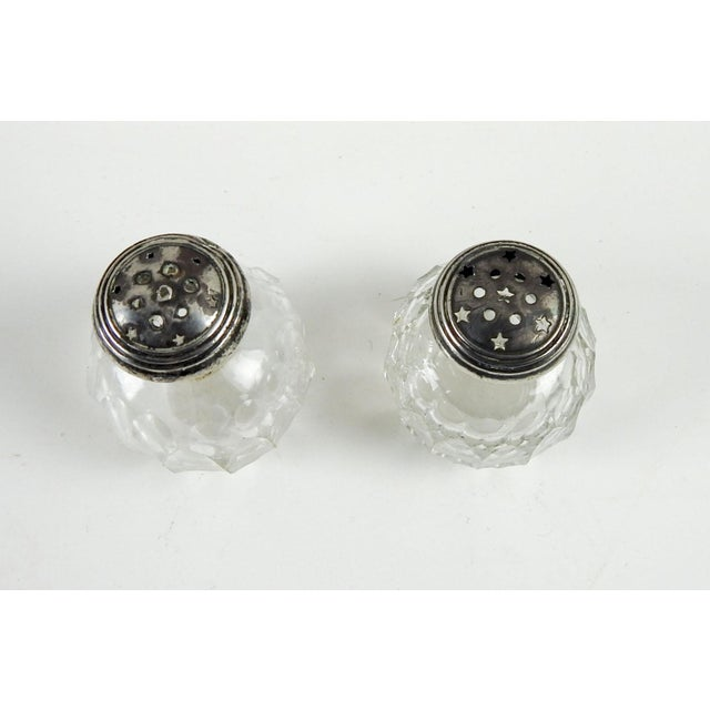 Set of small cut crystal salt and pepper shakers with sterling tops, circa 1910. Salt slightly larger that pepper and has...