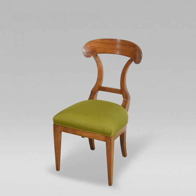 The arched back with cross stretcher above an upholstered seat with square tapering legs.