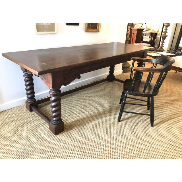 A Jacobean style carved solid oak refectory table the rectangular top with hand hewn edges and breadboard ends, over a...