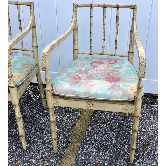 A stunning pair of faux bamboo Chippendale style paint decorated armchairs with cane seats and cushions. Painted to look...