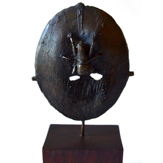 A fascinating and well executed bronze sculpture of a mask with a spider, bought in France. unsigned and on a wood stand....