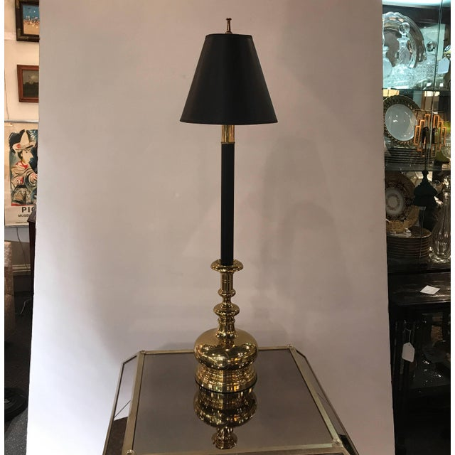 A handsome pair of cast brass tall candlestick lamps by Chapman. The gold foil lined parchment shades above a black...