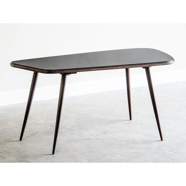 This chic vintage French coffee table circa 1950 has an attenuated appearance because of its slender black legs set at an...