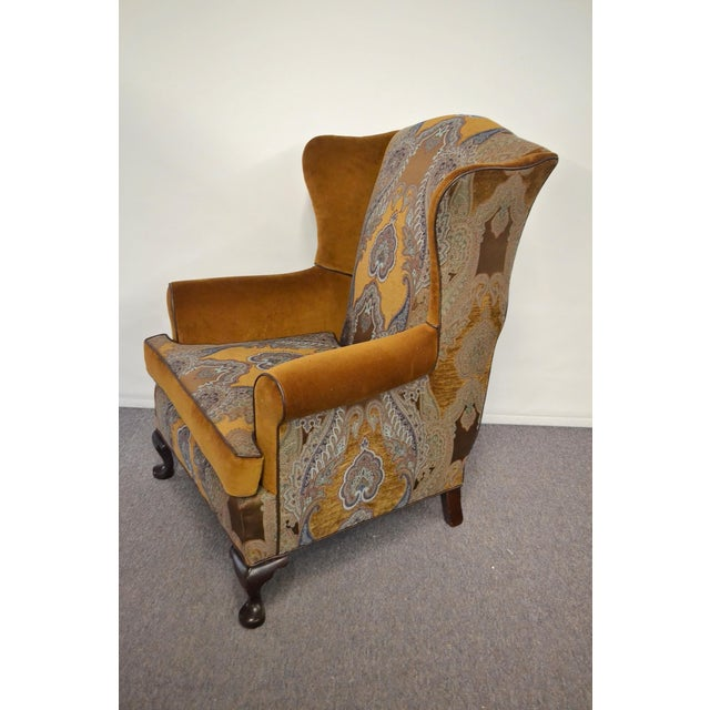 Vintage wingback chair upholstered in paisley woven fabric, velvet, and faux leather welting. All new materials. Wood legs.