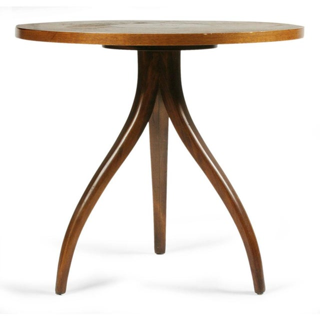 A dynamic occasional table comprising a circular top with a marquetry rosewood geometric hexagon design, resting on three...